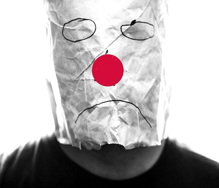 Quelle: Wikipdia, Gray_paper_bag_with_sad_smiley_over_head_with_red_nose by Mistermundo